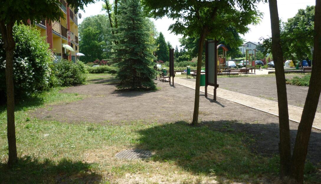 Na zdjęciu blok mieszkalny na osiedlu Czaplinieckim w Bełchatowie, trawnik i drzewa.